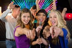 Amis féminins chantant la chanson ensemble dans la barre Photographie stock libre de droits