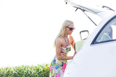 Amis féminins chargeant le bagage dans le tronc de voiture contre le ciel clair Photo stock