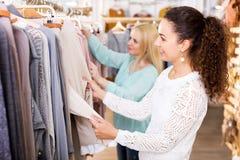 Amis féminins choisissant de nouveaux dessus dans la boutique Image stock
