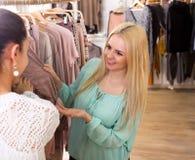 Amis féminins choisissant de nouveaux dessus dans la boutique Photos stock