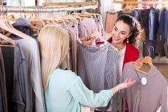 Amis féminins choisissant de nouveaux dessus dans la boutique Images stock