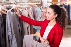 Amis féminins choisissant de nouveaux dessus dans la boutique Images libres de droits
