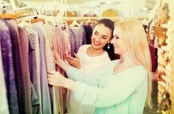 Amis féminins choisissant de nouveaux dessus dans la boutique Photographie stock