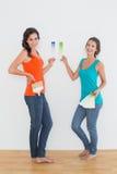 Amis féminins choisissant la couleur dans une nouvelle maison Images stock