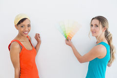 Amis féminins choisissant la couleur pour peindre une salle Photographie stock libre de droits