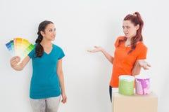 Amis féminins choisissant la couleur pour peindre une salle Photos stock