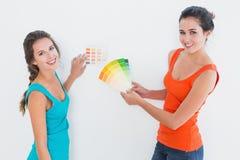 Amis féminins choisissant la couleur pour peindre une salle Photo libre de droits