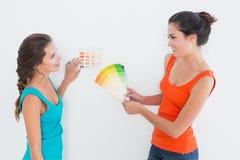 Amis féminins choisissant la couleur pour peindre une salle Image libre de droits
