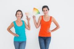 Amis féminins choisissant la couleur pour peindre une salle Photos libres de droits