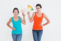 Amis féminins choisissant la couleur pour peindre une salle Images stock