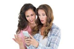 Amis féminins choqués regardant le téléphone portable Photographie stock libre de droits