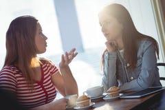 Amis féminins communiquant au café Photo libre de droits