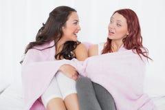 Amis féminins couverts en feuille tout en causant sur le lit Photo stock