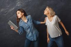 Amis féminins curieux à l'aide du comprimé au fond foncé de studio Photos libres de droits