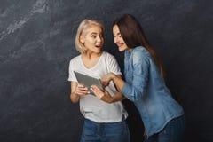 Amis féminins curieux à l'aide du comprimé au fond foncé de studio Image libre de droits