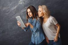 Amis féminins curieux à l'aide du comprimé au fond foncé de studio Images libres de droits