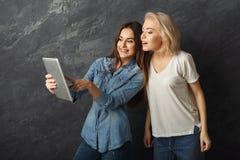 Amis féminins curieux à l'aide du comprimé au fond foncé de studio Image stock