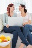 Amis féminins décontractés à l'aide de l'ordinateur portable à la maison Photos stock