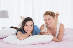 Amis féminins décontractés avec se situer à télécommande dans le lit Images stock