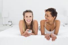 Amis féminins décontractés avec se situer à télécommande dans le lit Photos stock