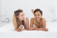 Amis féminins décontractés avec se situer à télécommande dans le lit Photos libres de droits