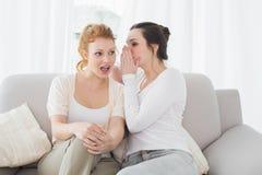 Amis féminins décontractés bavardant dans le salon Photographie stock