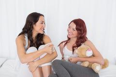 Amis féminins décontractés causant au-dessus du café dans le lit Images stock