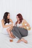 Amis féminins décontractés causant au-dessus du café dans le lit Image stock