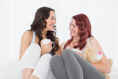 Amis féminins décontractés causant au-dessus du café dans le lit Photo stock