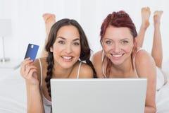Amis féminins décontractés faisant des achats en ligne dans le lit Images stock