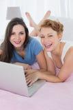 Amis féminins décontractés heureux à l'aide de l'ordinateur portable dans le lit Images libres de droits
