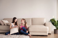 Amis féminins détendant dans le salon avec des téléphones Image stock