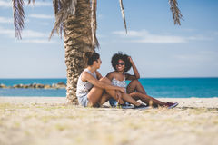 Amis féminins détendant sur parler de plage Image libre de droits
