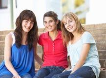 Amis féminins d'adolescent s'asseyant sur des opérations d'université Photo libre de droits