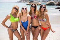 Amis féminins dans des bikinis froissant tout en se tenant à la plage Photographie stock libre de droits