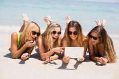 Amis féminins dans des bikinis souriant tout en regardant dans le comprimé numérique Image stock