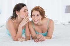 Amis féminins dans des dessus de réservoir bavardant dans le lit Photo stock