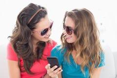 Amis féminins dans des lunettes de soleil lisant le message textuel Image libre de droits