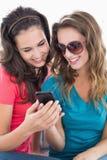 Amis féminins dans des lunettes de soleil lisant le message textuel Photographie stock libre de droits