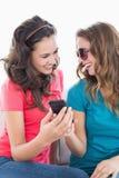Amis féminins dans des lunettes de soleil lisant le message textuel Image stock