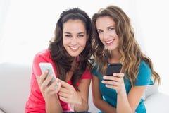 Amis féminins dans des lunettes de soleil lisant le message textuel Photos libres de droits