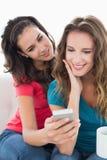 Amis féminins dans des lunettes de soleil lisant le message textuel Photo stock