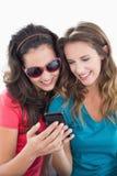 Amis féminins dans des lunettes de soleil lisant le message textuel Images libres de droits