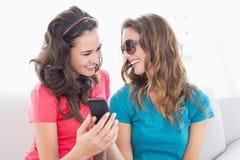Amis féminins dans des lunettes de soleil lisant le message textuel Photo libre de droits