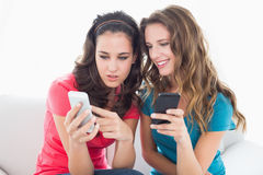 Amis féminins dans des lunettes de soleil lisant le message textuel Photos stock