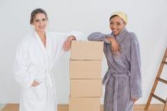 Amis féminins dans des peignoirs par des boîtes dans la nouvelle maison Photo libre de droits