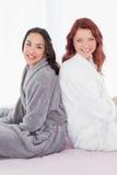 Amis féminins dans des peignoirs se reposant de nouveau au dos sur le lit Photographie stock