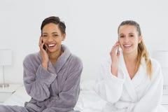 Amis féminins dans des peignoirs utilisant des téléphones sur le lit Photos stock