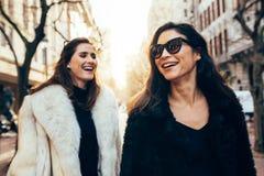 Amis féminins dans des vêtements chauds marchant sur la rue de ville Photo libre de droits