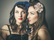 Amis féminins dans des vêtements de vintage avec le téléphone Images libres de droits